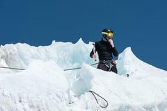 Un alpiniste professionnel dans un masque de casque et de ski sur l'assurance entaille la hache de glace dans le glacier Le trava image libre de droits