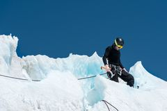 Un alpiniste professionnel dans un masque de casque et de ski sur l'assurance entaille la hache de glace dans le glacier Le trava photo libre de droits