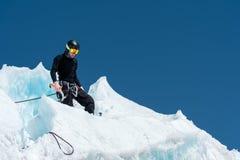 Un alpiniste professionnel dans un masque de casque et de ski sur l'assurance entaille la hache de glace dans le glacier Le trava images stock