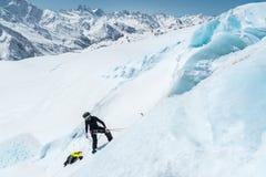 Un alpiniste professionnel dans un masque de casque et de ski sur l'assurance entaille la hache de glace dans le glacier Le trava images libres de droits