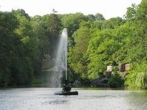 Un'alta corrente di una battitura della fontana in mezzo alla superficie dell'acqua dello stagno con i turisti sulla riva e Fotografia Stock