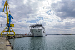 Un'alta gru del porto in blu ed in giallo contro lo sfondo di un cielo drammatico e di grande nave bianca Fotografie Stock Libere da Diritti
