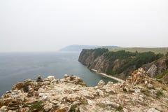 Un'alta linea costiera rocciosa una scogliera in mare un lago e una nebbia sopra l'acqua Fotografie Stock Libere da Diritti