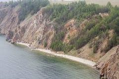 Un'alta linea costiera rocciosa una scogliera in mare un lago e una nebbia sopra l'acqua Fotografia Stock Libera da Diritti
