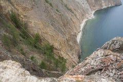 Un'alta linea costiera rocciosa una scogliera in mare un lago e una nebbia sopra l'acqua Fotografia Stock