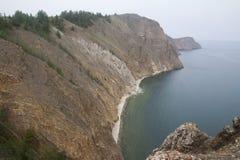 Un'alta linea costiera rocciosa una scogliera in mare un lago e una nebbia sopra l'acqua Fotografie Stock