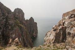 Un'alta linea costiera rocciosa una scogliera nel mare un lago e una nebbia sopra l'acqua Fotografie Stock Libere da Diritti