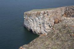 Un'alta linea costiera rocciosa una scogliera nel mare un lago e una nebbia sopra l'acqua Immagini Stock Libere da Diritti