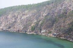 Un'alta linea costiera rocciosa una scogliera nel mare un lago e una nebbia sopra l'acqua Immagine Stock