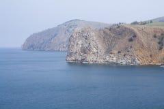 Un'alta linea costiera rocciosa una scogliera nel mare un lago e una nebbia sopra l'acqua Fotografia Stock Libera da Diritti