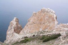 Un'alta linea costiera rocciosa una scogliera nel mare un lago e una nebbia sopra l'acqua Fotografia Stock