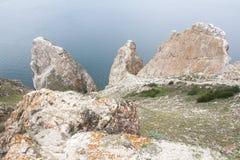 Un'alta linea costiera rocciosa una scogliera nel mare un lago e una nebbia sopra l'acqua Immagine Stock Libera da Diritti