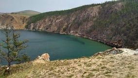 Un'alta linea costiera rocciosa una scogliera nel mare un lago e una nebbia sopra l'acqua Immagini Stock