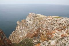 Un'alta linea costiera rocciosa una scogliera nel mare una nebbia del lago sopra l'acqua Immagine Stock