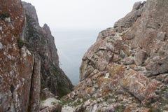 Un'alta linea costiera rocciosa una scogliera nel mare una nebbia del lago sopra l'acqua Fotografia Stock