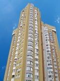 Un alto edificio urbano, ladrillo amarillo, cielo azul Fotografía de archivo