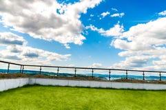 Un alto patio della villa con il recinto di vetro moderno e l'erba verde al sole con una trascuratezza di lusso di vista di panor immagine stock