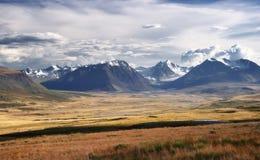 Un altopiano River Valley con erba gialla su un fondo delle montagne e dei ghiacciai innevati Fotografia Stock