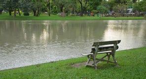 Un'altra vista della sedia di legno di A che disponendo accanto al lago ha creato uno scenico turbato nell'ambito della luce dell Fotografia Stock Libera da Diritti