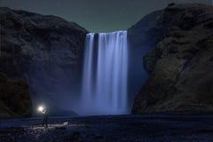Un alza que se coloca debajo de la cascada de Skogafoss en la noche Imagen de archivo