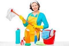 Un ama de casa joven con una fregona y los agentes de limpieza fotografía de archivo libre de regalías