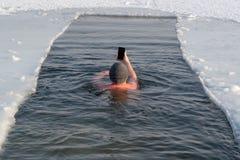 Un amante de la natación del invierno en un hoyo en el himse de las fotografías del hielo foto de archivo