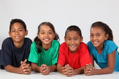 Un'amicizia di quattro scolari etnici felici Fotografie Stock