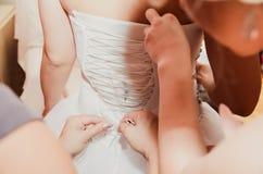 Un amico della sposa aiuta nella legatura del vestito fotografia stock libera da diritti