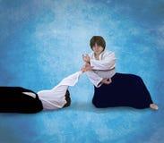 Un amo del Aikido realiza una técnica en un fondo del cielo azul Imágenes de archivo libres de regalías