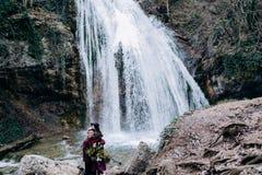 Un amore, coppia alla moda e giovane nell'amore sui precedenti di una cascata fotografia stock