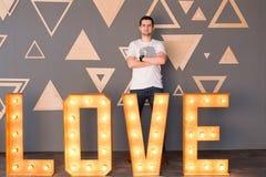 Un amour en bois de lettrage avec des ampoules et un garçon sur un fond Photographie stock libre de droits