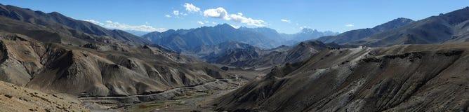 Un'ampia valle dell'alta montagna con una serie di marrone scuro colora, fra le rocce là è una strada grigia, la serpentina, il c Immagine Stock