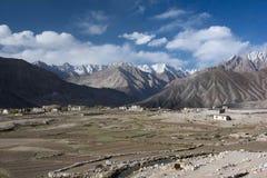 Un'ampia valle della montagna, nella priorità alta dei campi, ha separato dal lavoro in pietra, nei precedenti di una scogliera c Immagine Stock