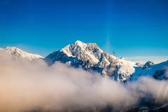 Un ampio panorama delle montagne di Snowy con alcune nuvole intorno, alpi del sud situate in isola del sud, in Nuova Zelanda Fotografie Stock