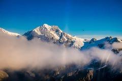 Un ampio panorama delle montagne di Snowy con alcune nuvole intorno, alpi del sud situate in isola del sud, in Nuova Zelanda Fotografie Stock Libere da Diritti