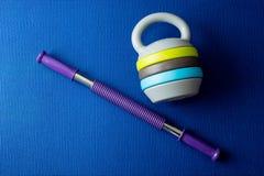 Un ampliador y un kettlebell ajustable en fondo azul de la estera de la yoga Fotografía de archivo