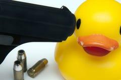 Un'anatra di gomma con una pistola alla sua testa fotografie stock