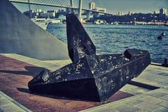 Un'ancora della nave sulla riva della baia Fotografie Stock Libere da Diritti