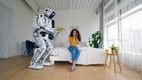 Un androïde apporte les pommes vertes à une fille tandis qu'elle parle à un téléphone Cyborg et concept humain clips vidéos