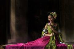 Un ange asiatique de conte de fées a orné avec des fleurs de lotus se reposant sur a images stock
