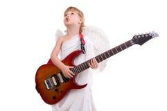 Un ange de garçon joue la guitare et chante Images libres de droits