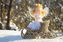 Un ange de jouet se repose dans un traîneau d'or sur la neige Jouets de Noël Photos libres de droits