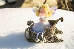 Un ange de jouet se repose dans un traîneau d'or sur la neige Jouets de Noël Image libre de droits