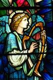 Un angelo che fa musica in vetro macchiato Immagini Stock Libere da Diritti