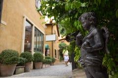 Un angolo bronzeo del bambino della statua nello stile italiano Immagini Stock