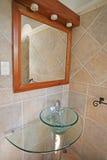Un angolo del bagno con uno specchio e un lavandino di vetro lanciano Immagine Stock Libera da Diritti