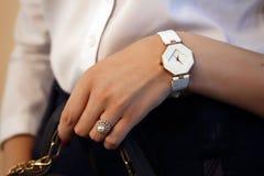 Un anillo con las piedras y un reloj en la mano de una muchacha imagen de archivo