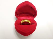 Un anillo de oro en una caja en forma de corazón Fotografía de archivo