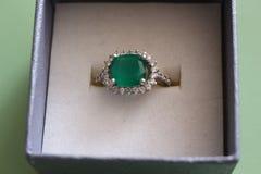 Un anillo de plata con una piedra verde grande y pequeño Fionites alrededor de él Imagen de archivo libre de regalías