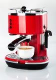 Un'annata rossa che guarda la macchina del caffè del caffè espresso sta producendo un caffè Fotografia Stock
